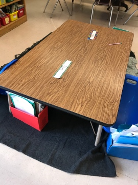 A low table allows students to sit on the floor while having a stable work surface.