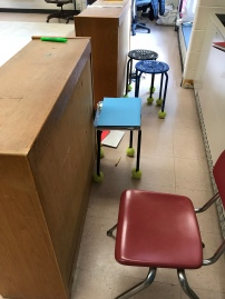 Low bookshelves provide standing students with a stable surface. Chairs and stools are present when little feet get tired.
